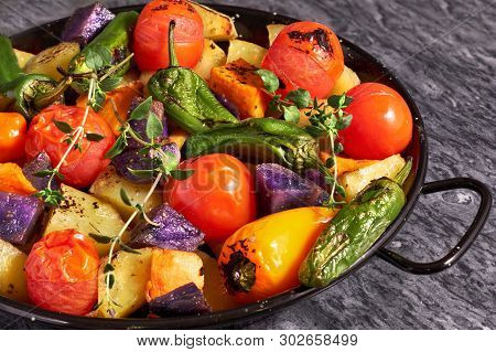Rustic Oven Baked Vegetables In Black Baking Dish Con Gray Stone Background. Seasonal Vegetarian Veg