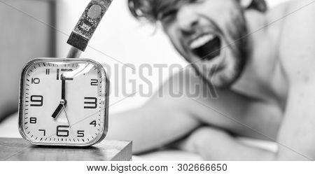 Annoying Ringing Alarm Clock. Man Bearded Annoyed Sleepy Face Lay Pillow Near Alarm Clock. Guy Knock