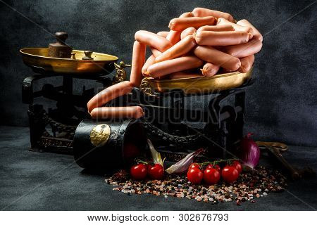 Large Pile Of Raw Long Wieners On Antiquarian Scales On Black