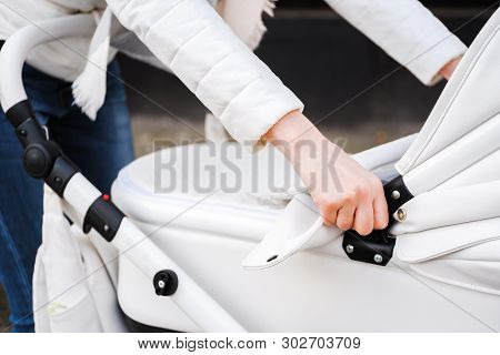 Woman strolling with white baby-carriage. Close up of female hands in white jacket adjust the canopy white baby-carriage. poster
