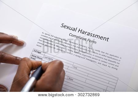 An Elevated View Of Human Hand Filling Sexual Harassment Complaint Form With Pen