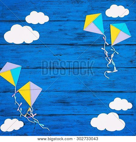 Paper Handmade Crafts: Clouds And Kites On The Blue Wood Background. Top View, Copy Space.