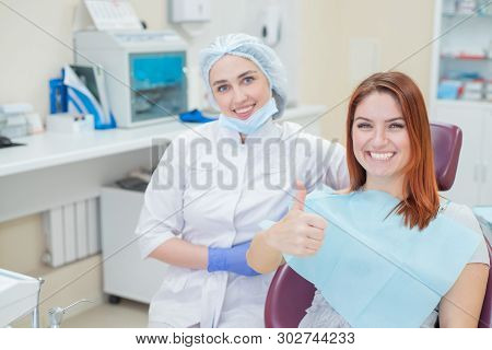 Happy Women A Dentist And Patient After Treating Teeth At The Dental Office, Smiling And Looking Tow