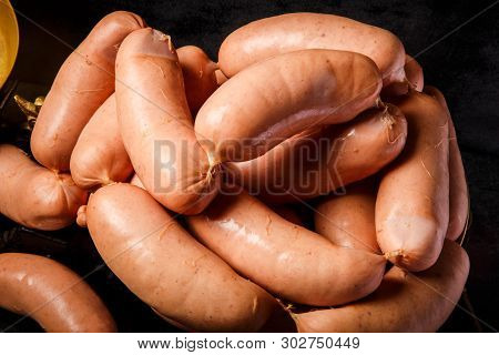 Closeup Heap Of Raw Short Thick Wieners Rolled In Spiral On Scales