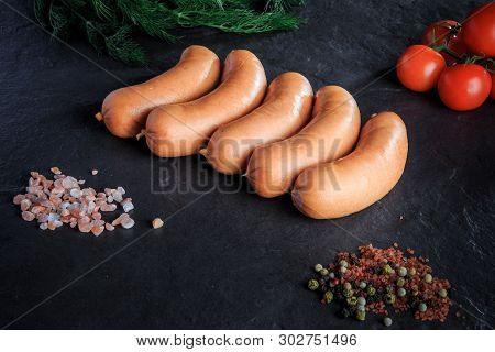 Top View Row Of Short Thick Sausages With Dill And Tomatoes