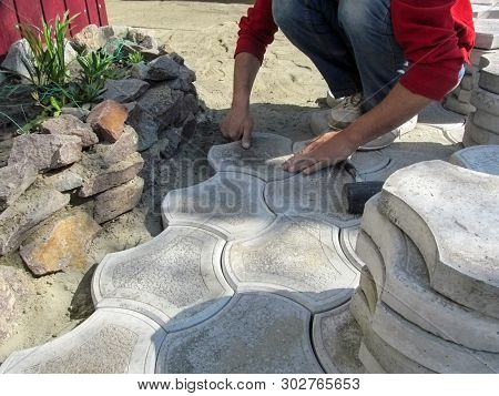 Worker By His Hands Lays Figured Paving Tiles Around A Flower Bed, Background With Copy Space. Beaut