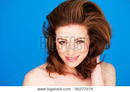 Smiling woman gazing directly into the camera with lovely red auburn hair.