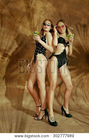 Beautiful young girls full-length portrait isolated on braun studio background with the palm shadows. Women posing in fashionable bodysuit. Facial expression, summer, weekend concept. Trendy colors. poster