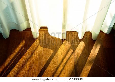 Shine Light Through The Curtains Of Blinds Closed The Door, The Morning Sun Shining Through The Curt