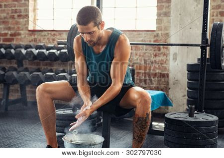 Fitness young man rubbing hands with chalk magnesium powder. Determined muscular guy preparing for weight lifting in gymnasium. Man clapping hands and preparing for workout at crossfit club.
