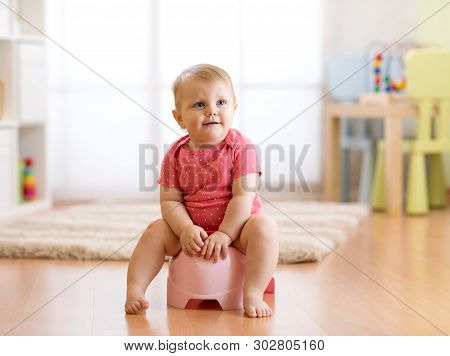 Little Smiling Baby Girl Sitting On A Pot. Isolated On White Background.