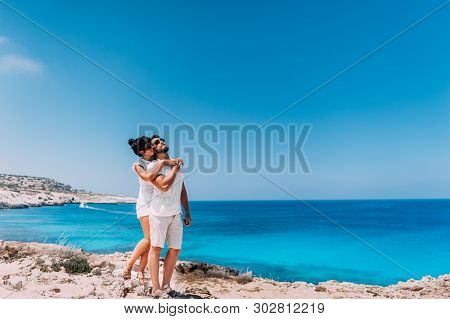 Happy Couple By The Sea. Man And Woman Hugging On The Beach. Honeymoon Lovers. Man And Woman On The