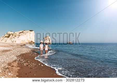 Happy Couple Holding Hands Walking On The Sandy Beach. Couple In Love At Sunset By The Sea. Couple I