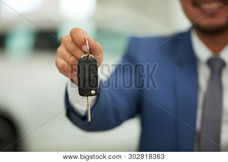 Closeup Of Car Owner Holding Car Key In His Hand And Showing It To The Camera In Car Showroom