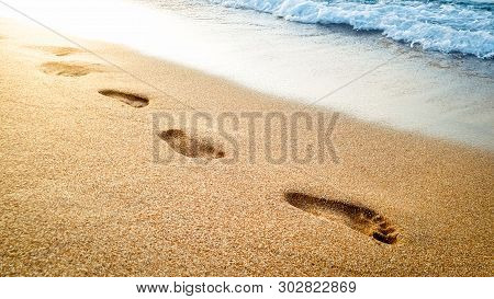 Closeup Beautiful Image Of Human Footprints On Wet Sand At Sea Beach Against Beautiful Sunset Over T