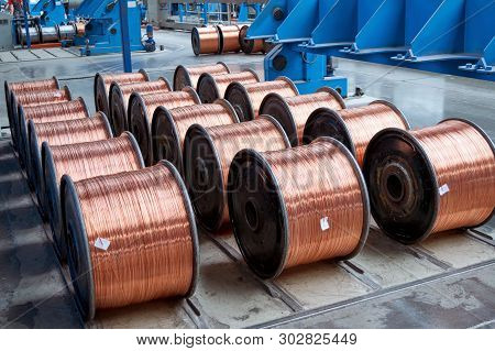 Several Rows Of New Finished Coils With Copper Wire In The Production Shop. Copper Wire Is Wound On