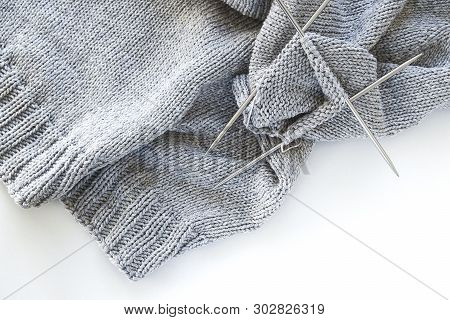 Incomplete knitting project with metal knitting needles close-up on a white background. Knitting a gray wool sweater. The concept of Hobbies, Creativity, crafts, handmade. poster