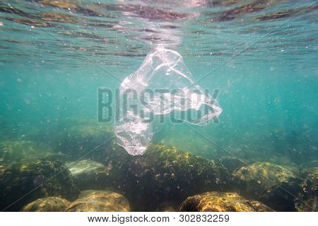 Plastic pollution: discarded plastic rubbish bag floats on tropical coral reef presenting a hazard to marine life poster