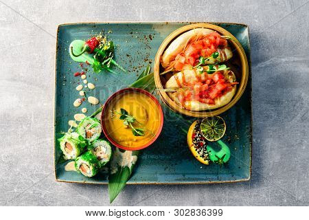 Bowl of wonton noodle soup and baozi on serving tray, flatlay on a dark grey stone background, copy space, asian food Bao buns and carrot soup, steam bun Bao Top view poster