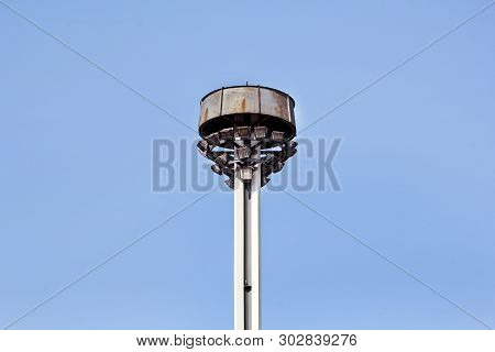 Tower With Reflectors At The Roundabout On The City Road And Street. Lighting Pole With Blue Sky. Bi
