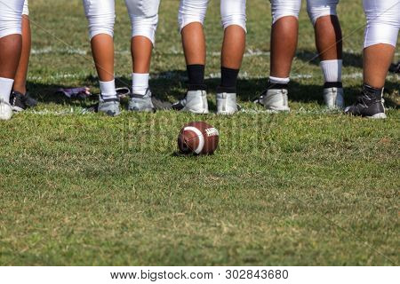 American Football Players Standing On Sideline Watching The Game