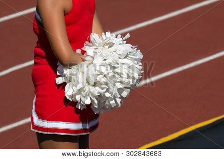 Cheerleader With Pom Poms On Sideline Of Football Game