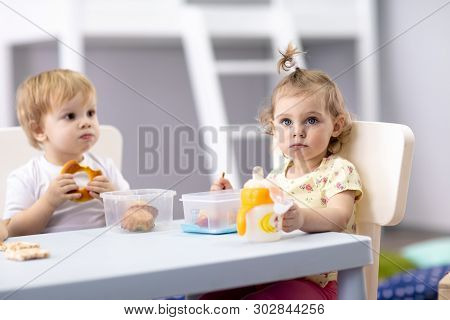 Time To Eat In Kindergarten. Babies Have A Lunch In Day Care Center