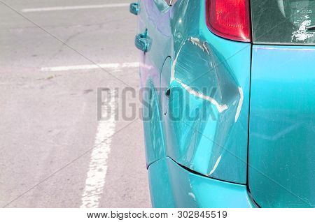 Damaged Car, Light Blue Scratched Car With Damaged Paint In Crash Accident Or Parking Lot And Dented