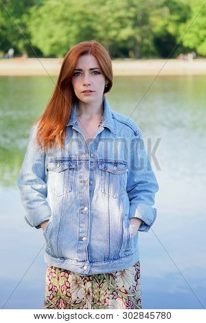Young Woman Wearing Denim Jacket Over Summer Dress Standing By Lake - Authentic Real People