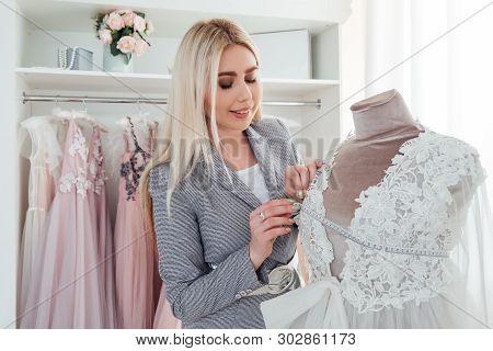 Luxury Showroom. Fashion Advisor Examining Designer Evening Dress From Latest Collection. Trendsette