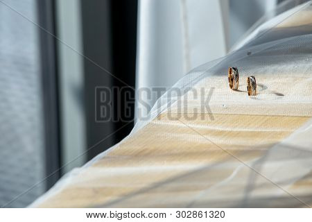 Two Wedding Rings On Wedding Veil. Gold Wedding Rings On The Background Of The White Bridal Veil. Ri