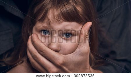 A Frightened Young Girl With A Grown Man's Hand Covering Her Mouth. Fear And Despair In The Child's