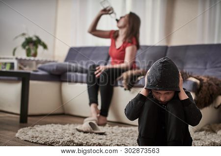 Mother Alcoholic Drinks Alcohol From A Bottle. The Child Is Closed From The Problem Of Drunkenness I