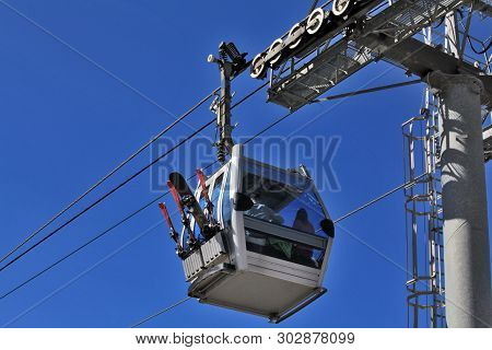 Against The Background Of The Ultramarine Spring Sky, A Young Pair Of Skiers In A Gondola Cabin Near