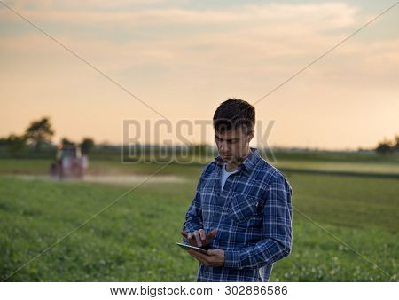 Attractive Young Farmer Working On Tablet In Field With Tractor Spraying Crops In Spring