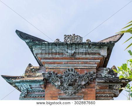 Dusun Ambengan, Bali, Indonesia - February 25, 2019: Decorated Top Of Pillar Set In Wall At Family C
