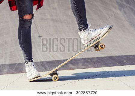 Skateboarder Legs Doing A Trick On Skateboard At Skate Park Outdoors