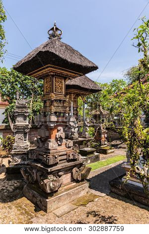 Dusun Ambengan, Bali, Indonesia - February 25, 2019: Decorated Stone Memorial Pillars At Family Comp