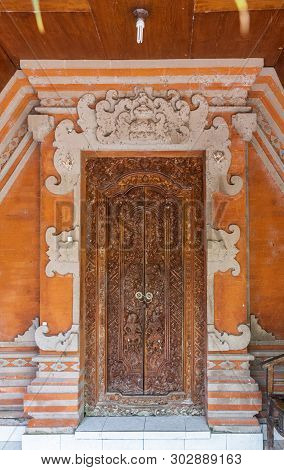Dusun Ambengan, Bali, Indonesia - February 25, 2019: Family Compound. Brown Decorated Door Of One Of