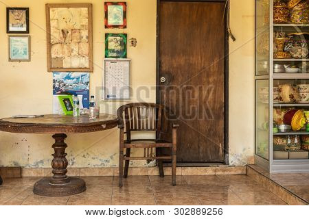 Dusun Ambengan, Bali, Indonesia - February 25, 2019: Family Compound. Brown Table, Chair And Door, S
