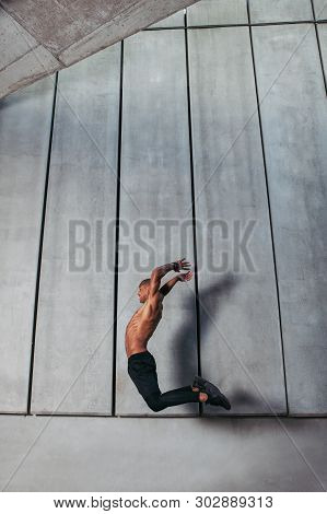 Sporty Young Man Jumping Against Concrete Wall