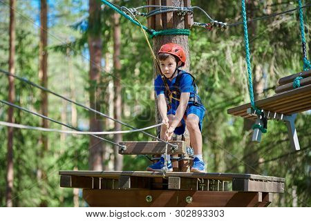 Cute Boy Enjoying Activity In Climbing Adventure Park At Sunny Summer Day. Safe Climbing With Helmet