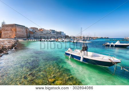 Several fishing boats at the Otranto harbour - coastal town in Puglia with turquoise sea. Italian vacation. Town Otranto, province of Lecce in the Salento peninsula, Puglia, Italy poster