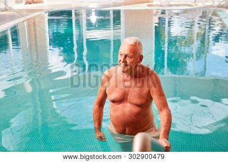 Senior man as a relaxed retiree in the swimming pool on a spa vacation