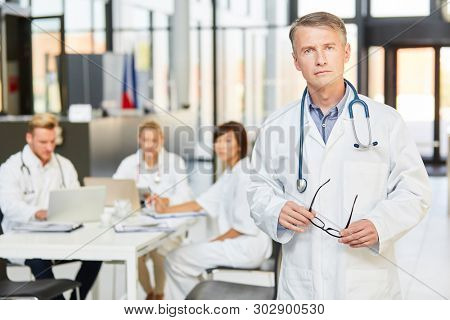 Man as a competent doctor and senior physician in front of his clinic team in a meeting