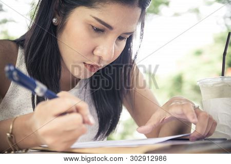 Young Woman Concentrate Reading Book. Girl Learning Writing Homework. Education Assessment Concept.