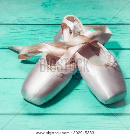 Pointe Shoes Ballet Dance Shoes With A Bow Of Ribbons Beautifully Folded On A Wooden Background.