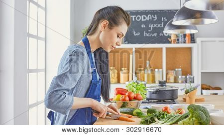 A Young Woman Prepares Food In The Kitchen. Healthy Food - Vegetable Salad. Diet. The Concept Of Die