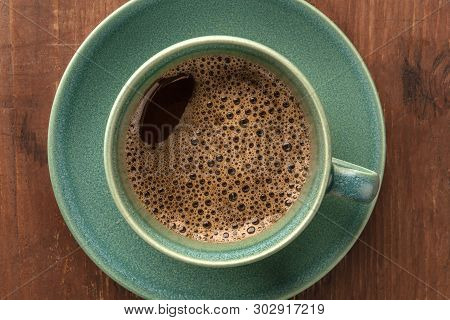 A Closeup Of A Cup Of Black Coffee, Shot From The Top On A Dark Rustic Wooden Background
