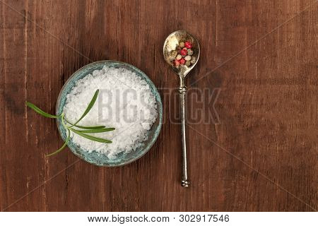 Gourmet Spices. Rosemary Infused Sea Salt And A Spoon With Pepper, Shot From Above On A Dark Rustic